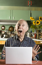 Shocked Senior Man In Dining Room With A Laptop Computer
