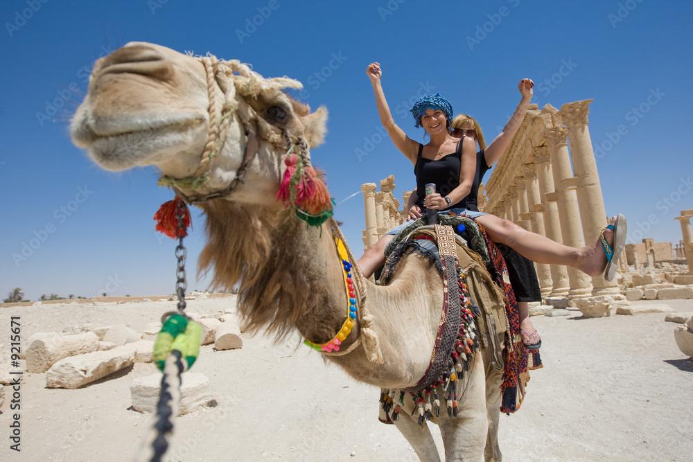 Fototapeta two girls are ride on camel in desert