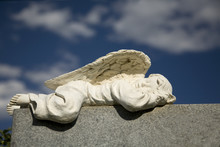 A Sleeping Angel Adorns A Granite Headstone.