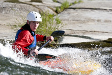 A Whitewater Kayaker Surfing O...