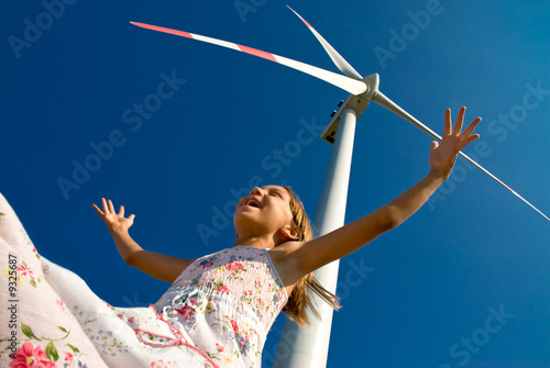 Fotografie, Obraz  child playing with the wind near a wind turbine