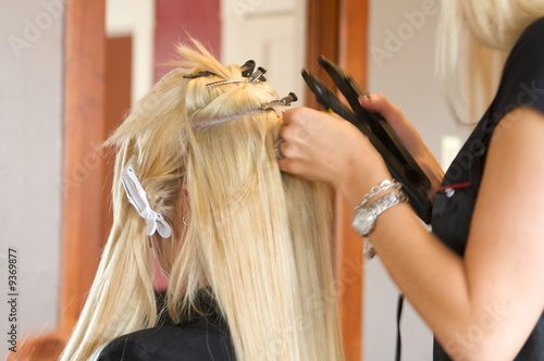 Fotografie, Obraz  Image of a hairdresser applying extensions to a client's hair