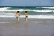 Jeunes femmes à la plage entrant dans les vagues.