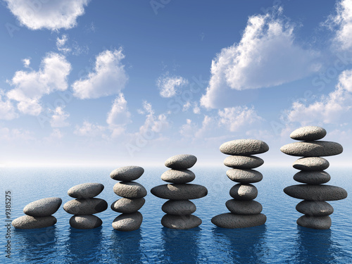 Foto Rollo Basic - A row of stones in water. A pebble on a background of the sky