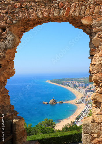 Photo  Blanes beach view through an arch  (Costa Brava, Spain)