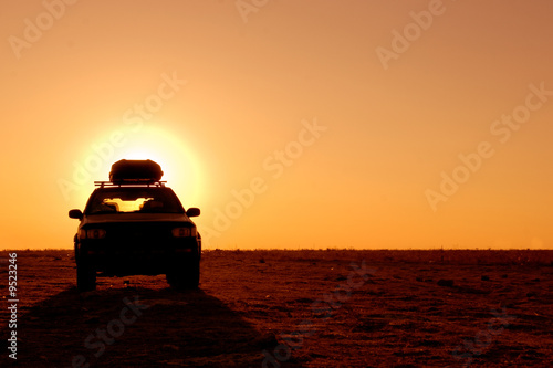 Valokuva Offroad 4x4 vehicle in the desert at sunrise