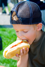 A Boy Eating A Hot Dog Outfoors