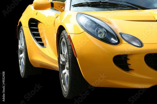 Foto auf Leinwand A Isolated yellow sports car on black