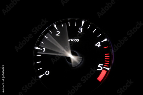 Photo  moving revs meter of a sports car on a black background.