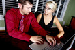 canvas print picture - Pretty blond and handsome man using a laptop together