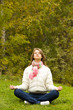Portrait of calm girl meditating outside in autumn
