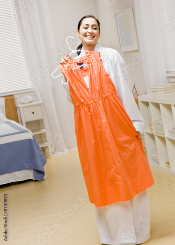 Woman in bathrobe examining glamorous dress