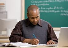 Teacher With Laptop Grading Papers In School Classroom