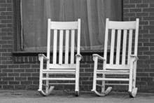 Empty White Rocking Chairs On City Street