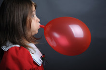 Little Girl Blowing A Red Balloon, Close Up Portrait