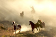 canvas print picture - Sunlight Horses and cowboy galloping and through the desert
