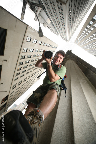 Etiqueta engomada - Photographer in New York City. Wide angle view from below.