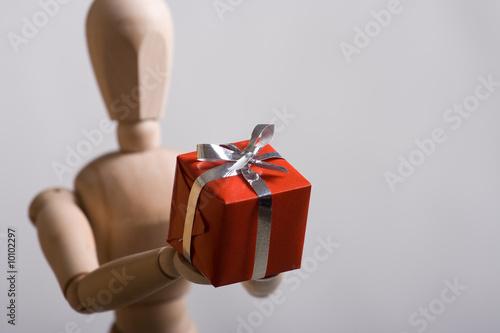 Valokuva  Wooden marionette presenting a red gift. Short DOF.