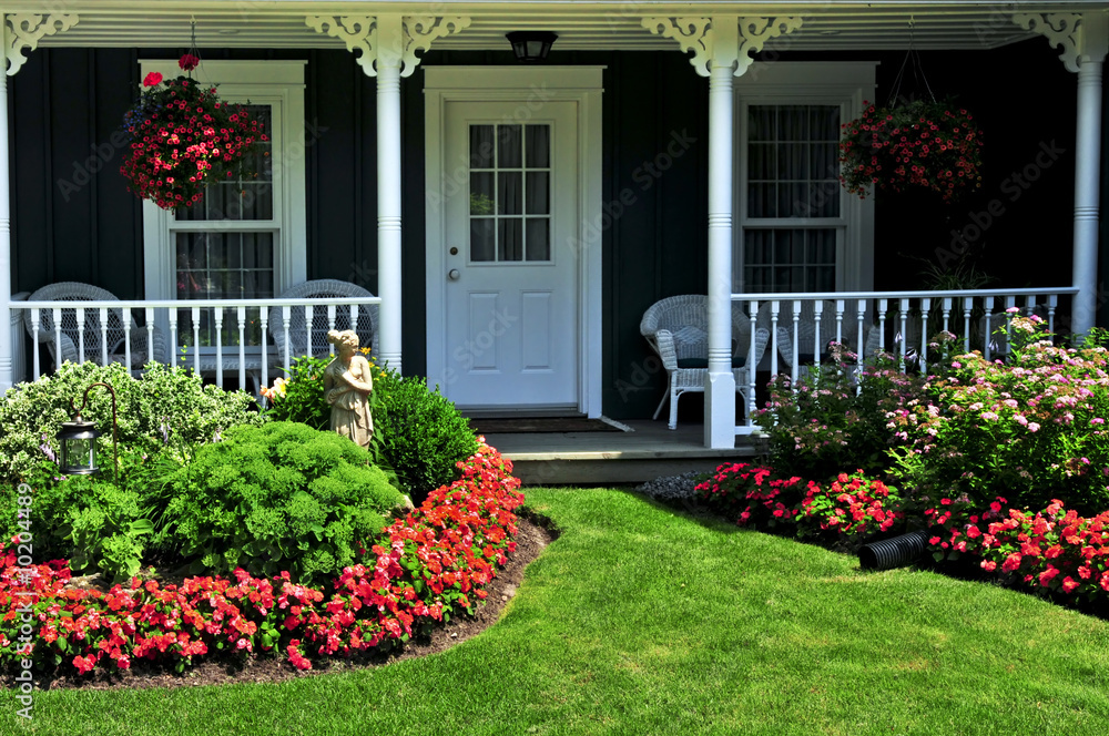 Fototapeta Landscaped front yard of a house with flowers and green lawn
