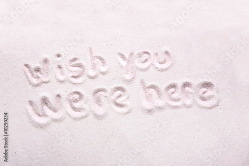 Photo  Wish you were here written in luxerious white sand