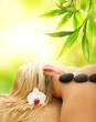 Leinwanddruck Bild Massage with volcanic hot stones