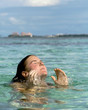 Young woman surfacing from clear green tropical water
