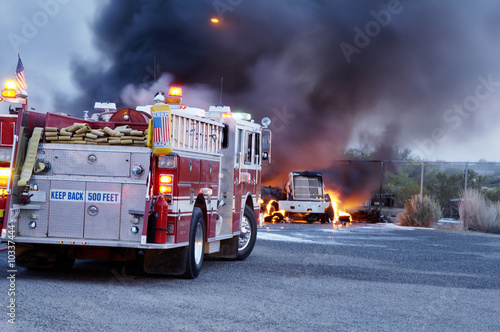 Firemen fight a fire that has involved  industrial trucks. Poster Mural XXL