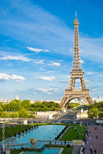 Fotografie, Obraz Eiffel Tower, with cloudy blue sky and sunny trees around.