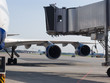 The plane on a runway with a gangway