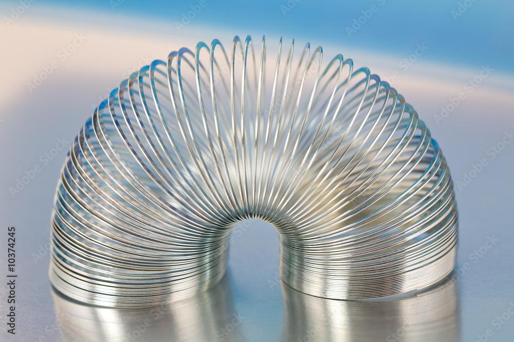 Fototapeta Steel Spring Toy on Shiny Blue Metallic Background