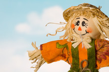 Fall Scarecrow Closeup Against Blue Sky With White Clouds