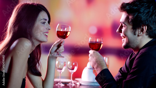 Foto op Canvas Restaurant Young couple celebrating with red wine at restaurant