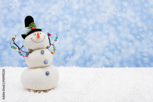 Snowman sitting on snow with snowflake background Poster