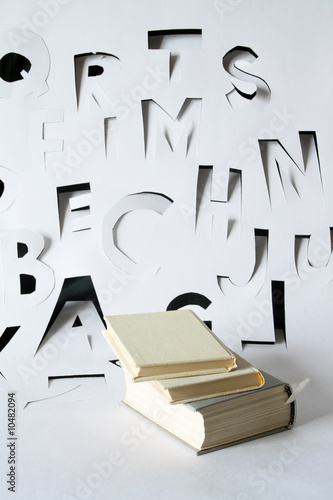 Books on background with letters made from papery sheet Canvas Print