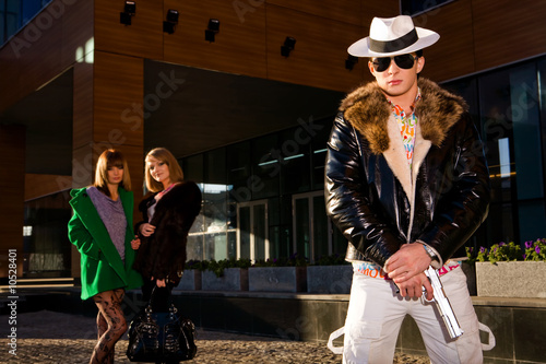 Fotografija  Stylish gangster with a gun and two young women on background