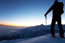 Backcountry Skier Reaching The Summit Of The Mountain