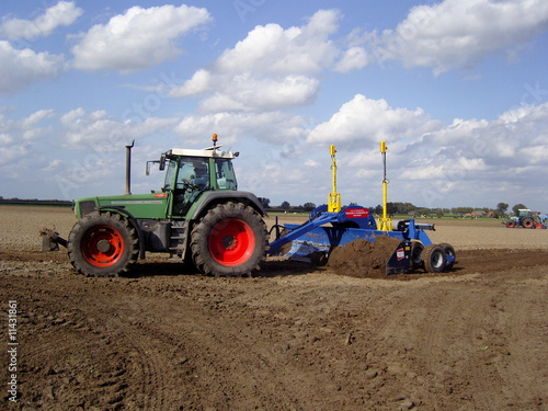 Photo ploughing the land with big agri culture machine