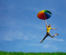 Flying Girl With Colorful Umbrella On The Blue Blue Sky