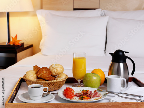 Fotografie, Obraz  Tray with breakfast on a bed in a hotel room.