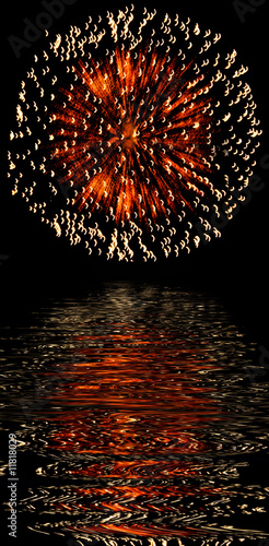 Explosive fireworks shooting into the black sky and reflections