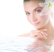 Beautiful Woman With Lily Flower  In Her Hair Reflected In Water