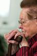 Gehbehinderte Seniorin mit Gehstock lächelnd