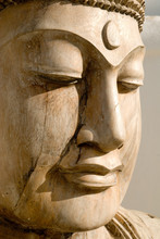 A Close Up Of A Carved Wooden Statue Of Buddha