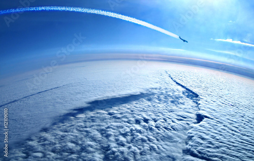 Fotografia  Airplane contrails in the blue sky above the clouds