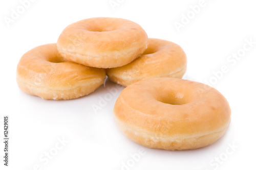 Valokuva Four doughnuts or donuts piled isolated on white.