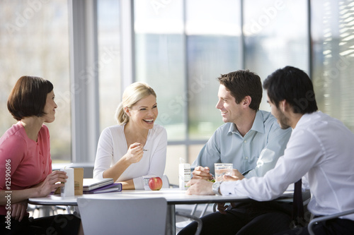 Fototapety, obrazy: Four office colleagues eating lunch in an office canteen or cafe