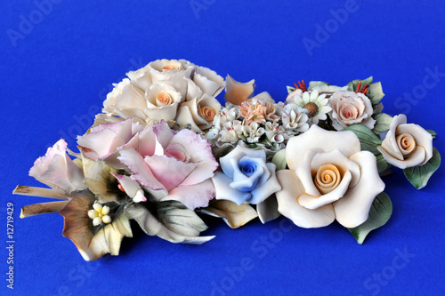 Valokuva  Bunch of ornamental ceramic flowers (like Capodimonte) on blue
