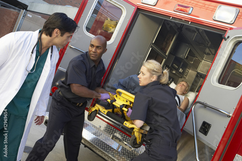 Photo Paramedics and doctor unloading patient from ambulance
