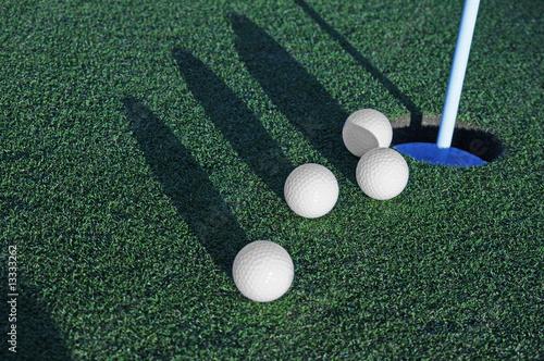 Fotografie, Obraz  Fore  golf balls rolling toward cup