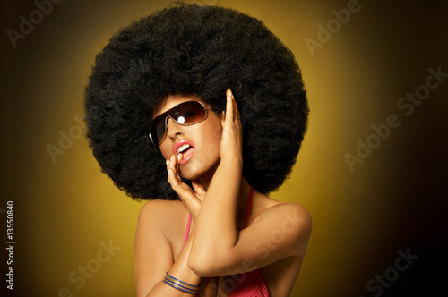 Beautiful woman with huge afro haircut on yellow Canvas Print